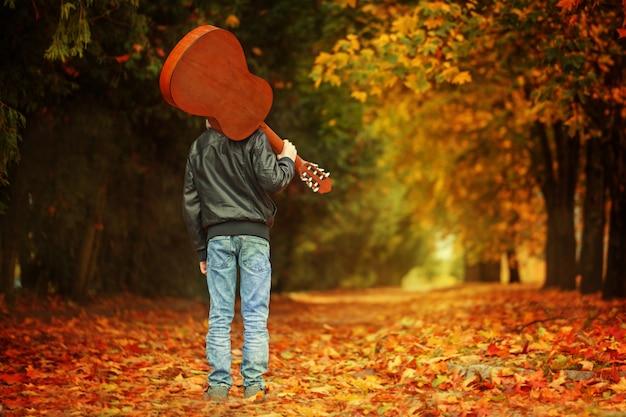 秋の道を歩いてギターを持つ少年。背面図