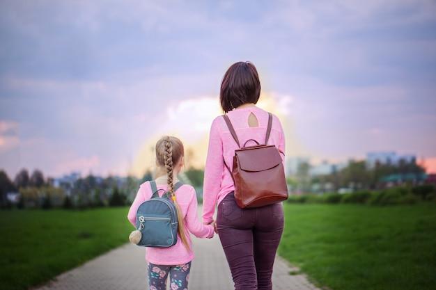 Мать и ее маленькая дочь с рюкзаком, прогулки в летний день. вид со спины.