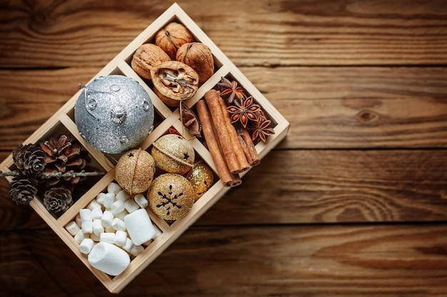 Деревянная коробка с елочными украшениями, шариками, колокольчиками, орехами, шишками, корицей, зефиром