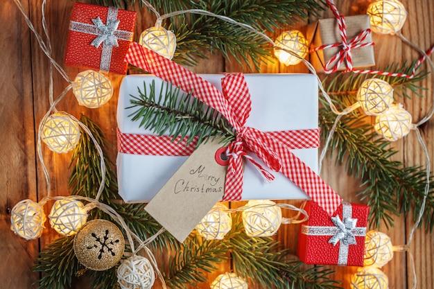 モミの枝、ジングルの鐘、小さなプレゼント、クリスマスライトのクリスマスギフトボックス。クリスマスと新年あけましておめでとうございます組成。上面図。
