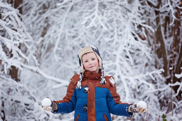 かわいい男の子、雪の中を歩く冬服の子供