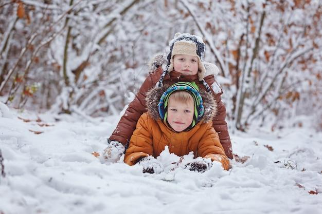 Два маленьких детей, мальчик братьев, играя и лежа в снегу на открытом воздухе во время снегопада. активный отдых с детьми зимой в холодные дни