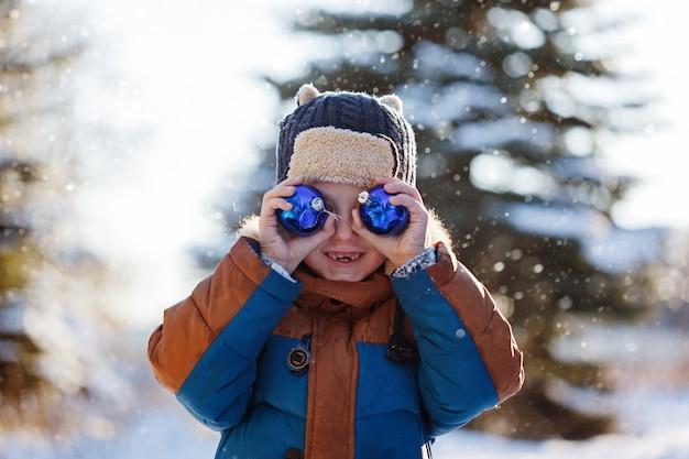 冬の自然の中を歩く少年の肖像画。雪で遊ぶ。コンセプト幸せな子供時代