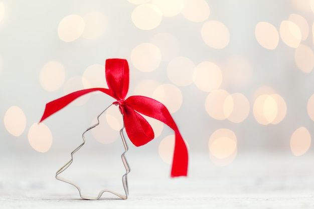 Резец печенья рождественской елки с красным смычком на белой предпосылке с космосом экземпляра. рождественская концепция