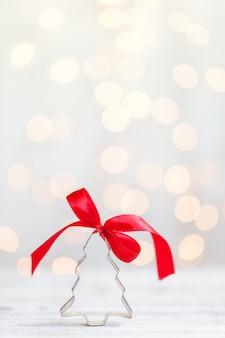 コピースペースで白い背景に赤の弓とクリスマスツリークッキーカッター。クリスマスのコンセプト。