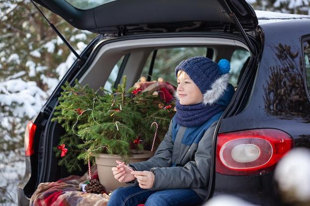 雪の降る冬の森で黒い車に座っているかわいい男の子。クリスマスのコンセプト。