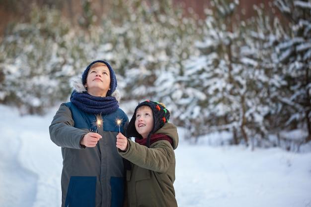Счастливая семья два брата держат бенгальские огни или бенгальские огни на открытом воздухе в красивом зимнем лесу.