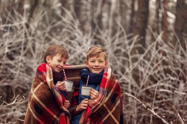 子供たちは冬の森で暖かい毛布の下でホットチョコレートを飲みます。クリスマス休暇。