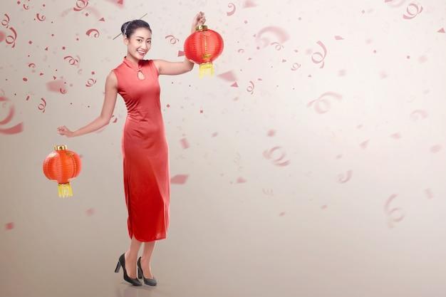 チャイニーズランタンを保持しているチャイナドレスを着ている若い中国人女性