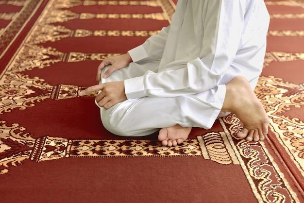 イスラム教徒の男性が神に祈りながら折り敷き