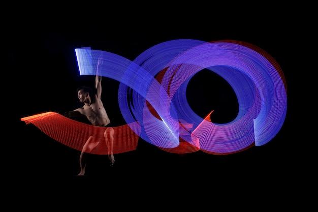 青と赤のライト効果で踊る若い男のバレエ