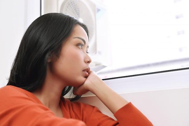 Портрет азиатской женщины мечтает и смотрит в окно