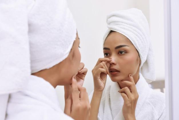 バスタオルを持つ若いアジア女性は彼女の顔を清潔にする