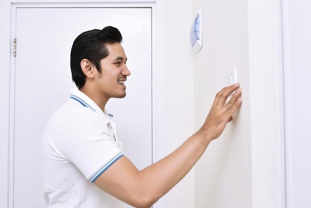 Красивый азиатский человек, выключив свет с настенным выключателем