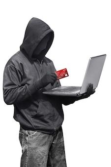 立っている間ラップトップとクレジットカードを保持している匿名のマスクを身に着けているハッカー男