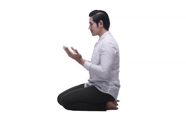 祈りながら座っている宗教的なアジアのイスラム教徒の男性