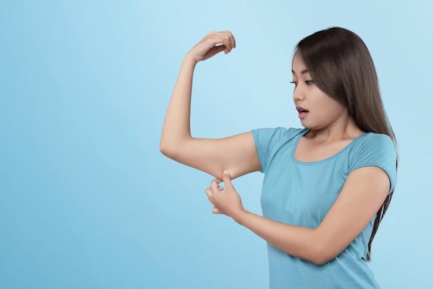 彼女の腕に筋肉を失う若いアジア女性