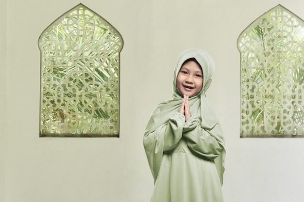 ヒジャーブの祈りを着ている陽気なアジアのイスラム教徒の少女