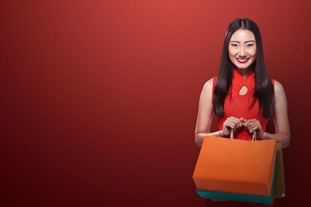 買い物袋を保持しているチャイナドレスの中国人女性
