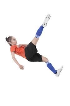 アジアの女性のフットボール選手はボールを蹴る