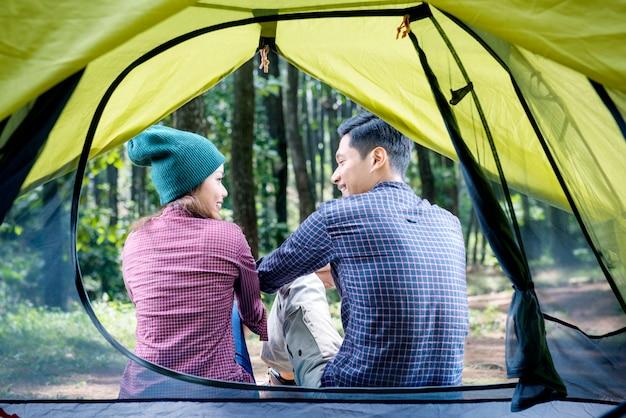 テントの外でリラックスしたアジアカップルの背面図