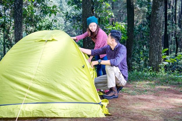 魅力的なアジアカップルはキャンプのためのテントをセットアップ