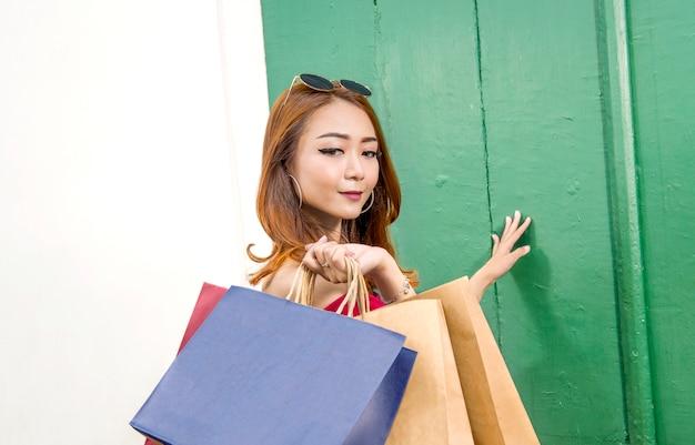 かなりアジアの女性が買い物袋でポーズ