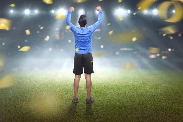 彼の勝利を祝っているアジア人の背面図