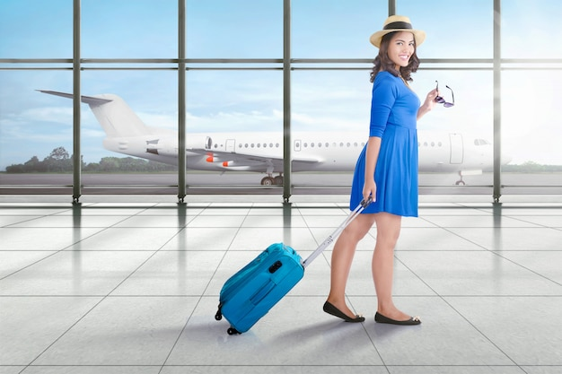 スーツケースを歩いて笑顔のアジア旅行者女性