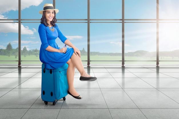 Красивая азиатская женщина сидя на чемодане пока ждущ самолет вылета