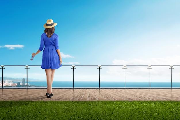 背面にアジアの旅行者の女性がバルコニーに立っています。