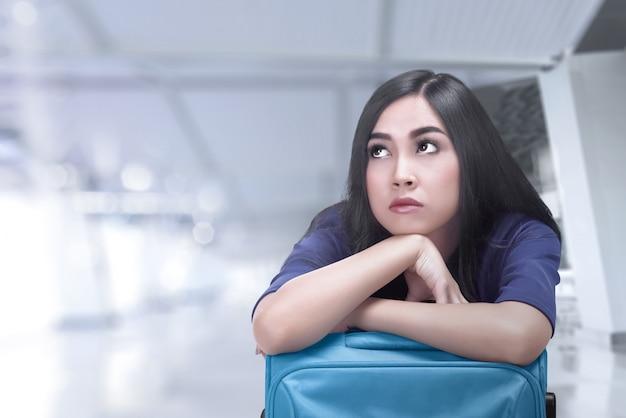 彼女の飛行を待っているスーツケースと退屈のアジア旅行者女性