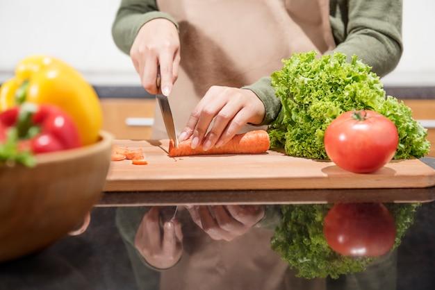ナイフで野菜を切る女性手のクローズアップ表示