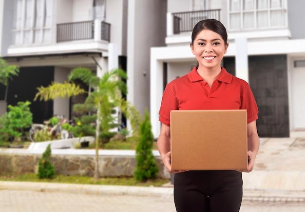 パッケージを提供する若いアジアの宅配便の女性