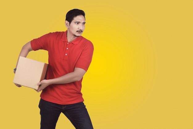 魅力的なアジアの男性配達は小包をもたらします