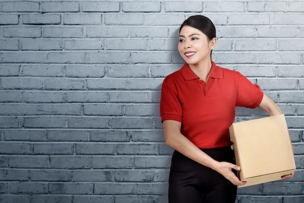 小包を運ぶ笑顔のアジアの配達女性