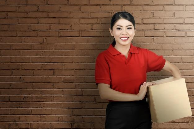 かなりアジアの宅配便の女性はパッケージをもたらす