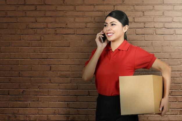 パッケージをもたらしながら携帯電話を使用して美しいアジアの配達の女性