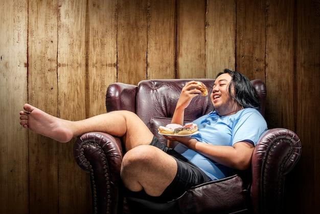 アジアのデブ男が皿にドーナツを食べる
