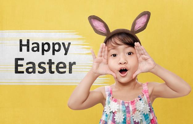 バニーの耳を持つかわいいアジアの女の子はハッピーイースターを祝う