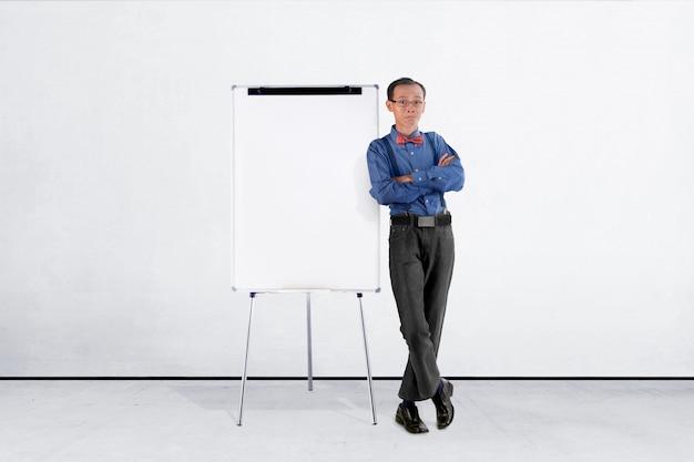 ホワイトボードに傾いている青いスーツのアジア系のビジネスマンの笑みを浮かべてください。