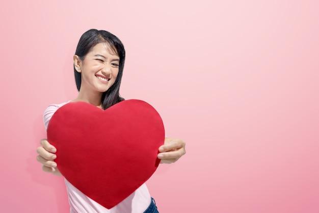 彼女の手に赤いハートを持つ若いアジア女性