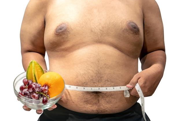 男はボウルにフルーツを保持し、測定テープで彼の胃を測定