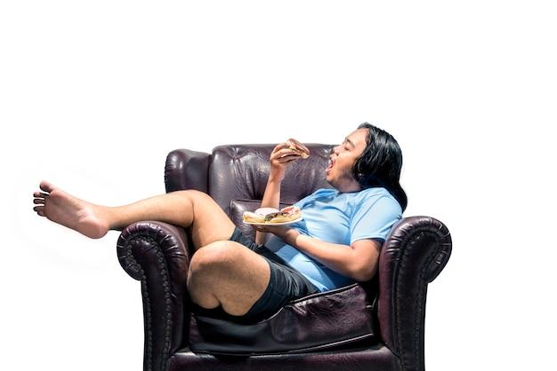 アジアのデブ男がソファにドーナツをスナック