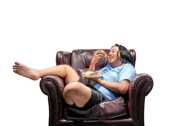 幸せなアジアのデブ男がソファの上の皿にドーナツをスナック