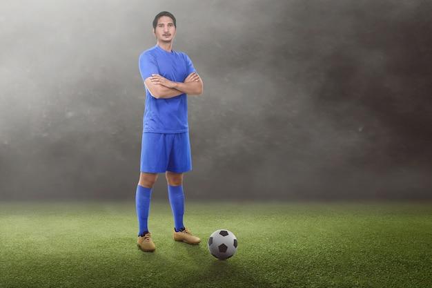 Красивый азиатский футболист со скрещенными руками