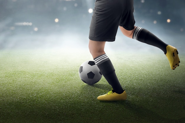 Футболист пытается ударить по мячу