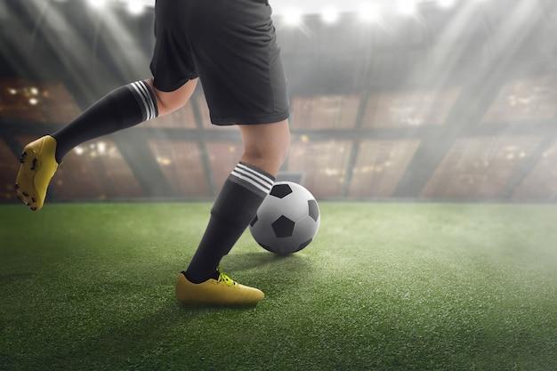 試合にボールを持つフットボール選手