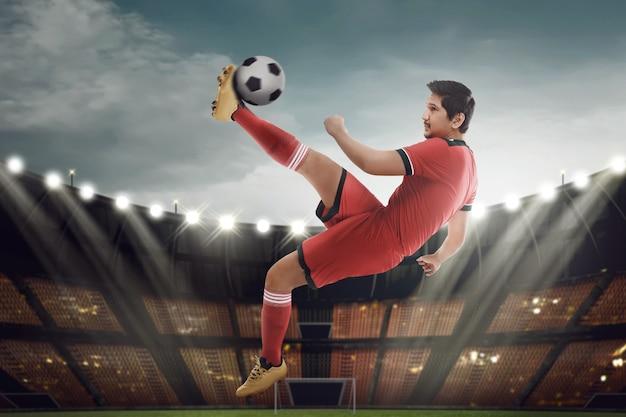 Мощный азиатский футболист бьет по мячу в воздухе