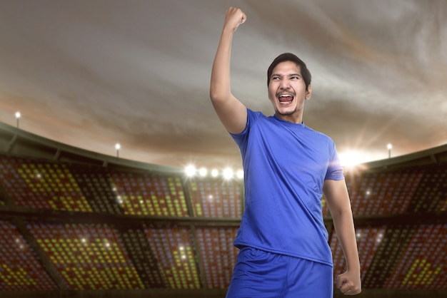 Возбужденный азиатский футболист с синим свитером празднует